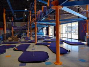 Indoor mini links course with purple turf and orange obstacles at Altitude Trampoline Park in Round Rock, TX.