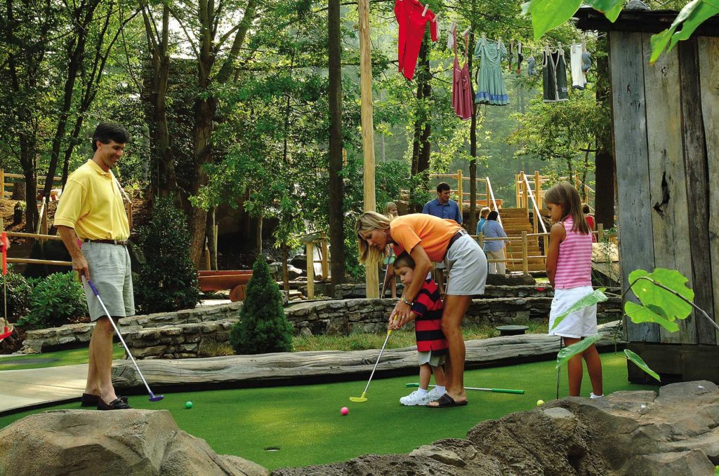 Mom helping son play mini golf on outdoor course in Gatlinburg