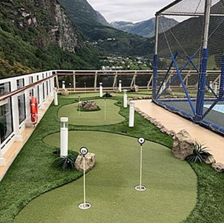 Adventure Golf & Sports miniature golf course on a cruise ship deck with mountains in the background