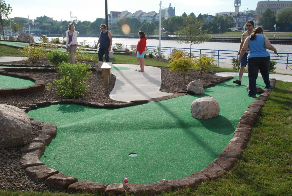 People enjoying outdoor miniature golf course hole at harbor pointe mini golf course in Sheboygan, WI