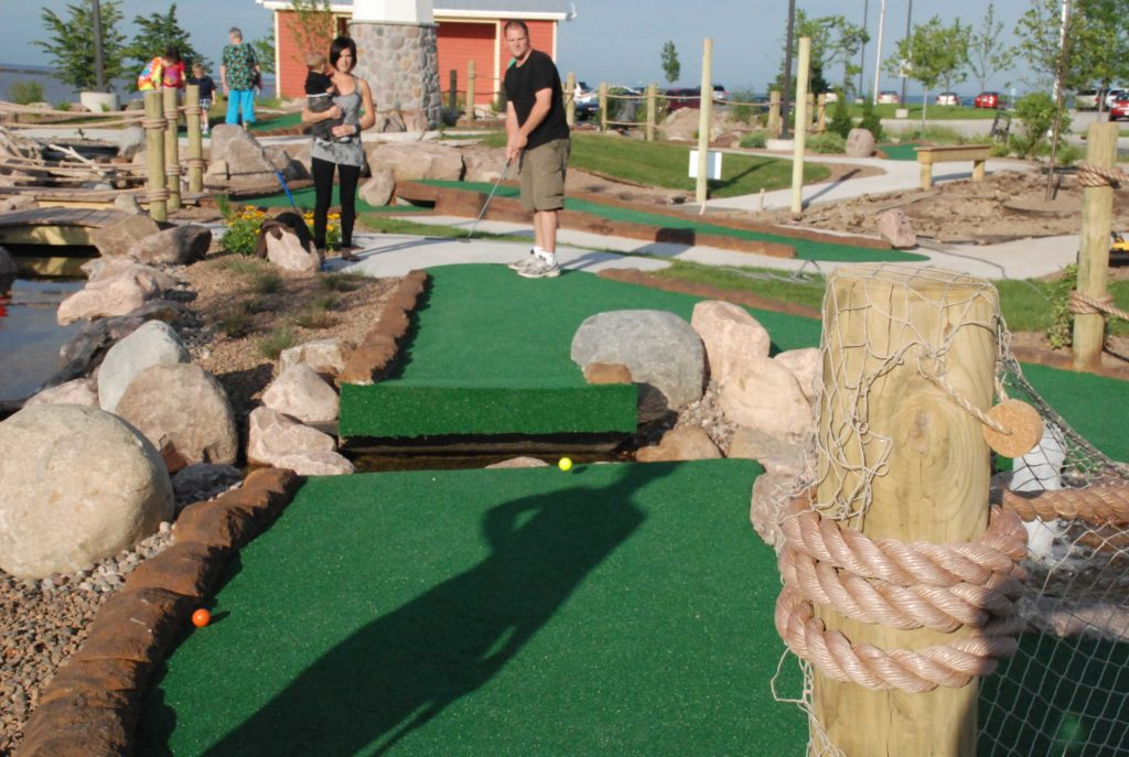 Couple playing mini golf on a sunny outdoor miniature golf course in Sheboygan Wisconsin