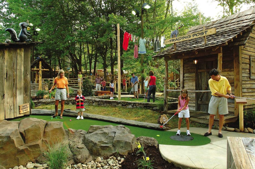 Family playing outdoor mini golf on Davey Crockett course in Tennessee