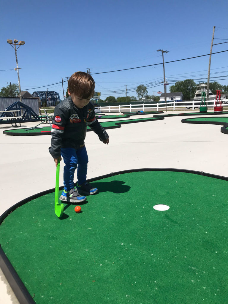Child prepares to putt on the 18-hole Anywhere Links, Jr.® mini golf course at Romp's Putter Port.